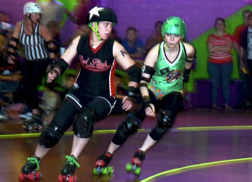 Red Stick's jammer Little Miss Maggot (left) and Las Tejanas jammer El A Dodgeher (right) race around the corner during the Alamo City roller Girls Season Opener between the Las Tejanas and Redstick Roller Deby at the Rollercade In San Antonio, Texas on March 11, 2012.