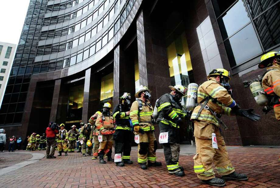 Firefighters prepare their gear outside the Columbia Center during the Scott Firefighter Stairclimb in Seattle on Sunday, March 11, 2012. 1,550 firefighters from the U.S., Canada and Germany participated in the climb, which requires participants to scale 69 flights of stairs and 1,311 steps equaling 788 ft. of vertical elevation. The annual climb is the largest in the world. Photo: LINDSEY WASSON / SEATTLEPI.COM