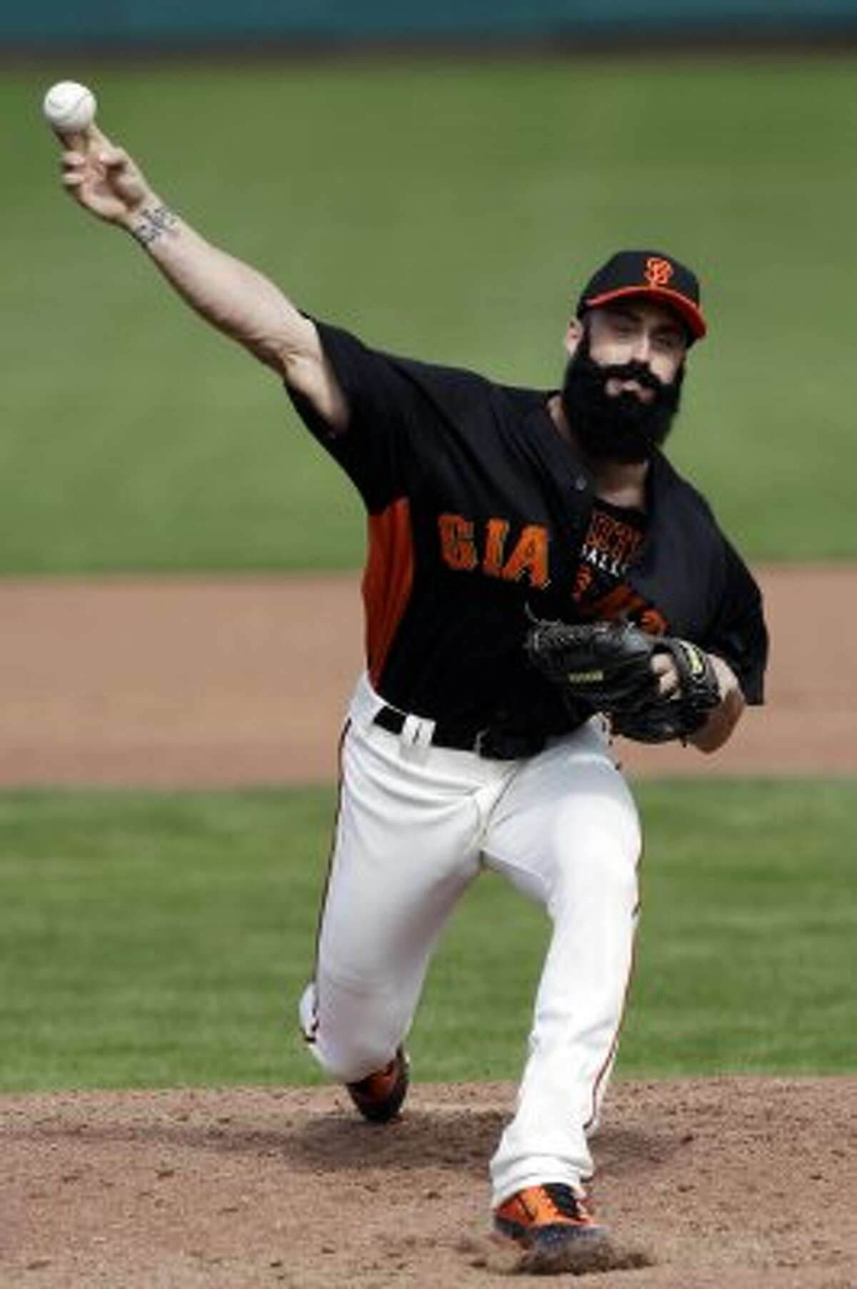 San Francisco Giants pitcher Brian Wilson throws to the Seattle Mariners during the fourth inning of a spring training baseball game. (Marcio Jose Sanchez / Associated Press)