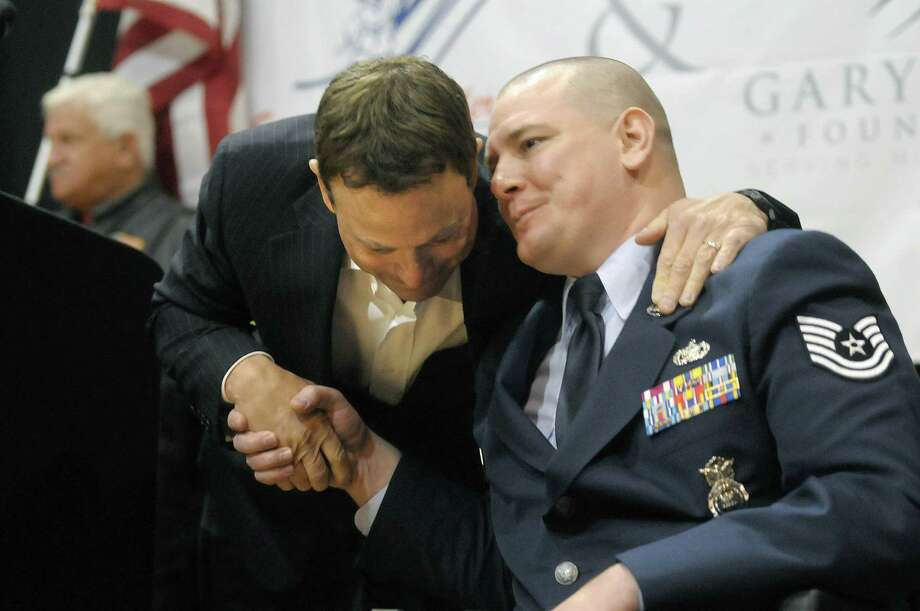 Actor Gary Sinise, left, embraces disabled veteran Joseph Wilkinson at the Washington Avenue Armory on Monday, March 12, 2012 in Albany, NY. The event was held to announce an April benefit concert, which includes musical performances by Gary Sinise and other, to help raise funds to build a home for disabled veteran Joseph Wilkinson and his family. The Stephen Siller tunnel to Towers Foundation and the Gary Sinise Foundation are the two groups involved in the building of homes for disabled veterans. Wilkinson served as a technical sergeant in Air Force Security Forces during the invasion of Iraq in 2003. (Paul Buckowski / Times Union archive) Photo: Paul Buckowski