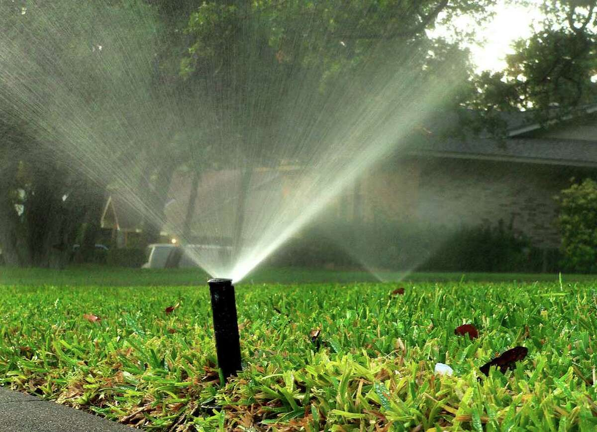 Sprinklers spray on a San Antonio lawn as the city continues under watering restrictions. (Express-News file photo)