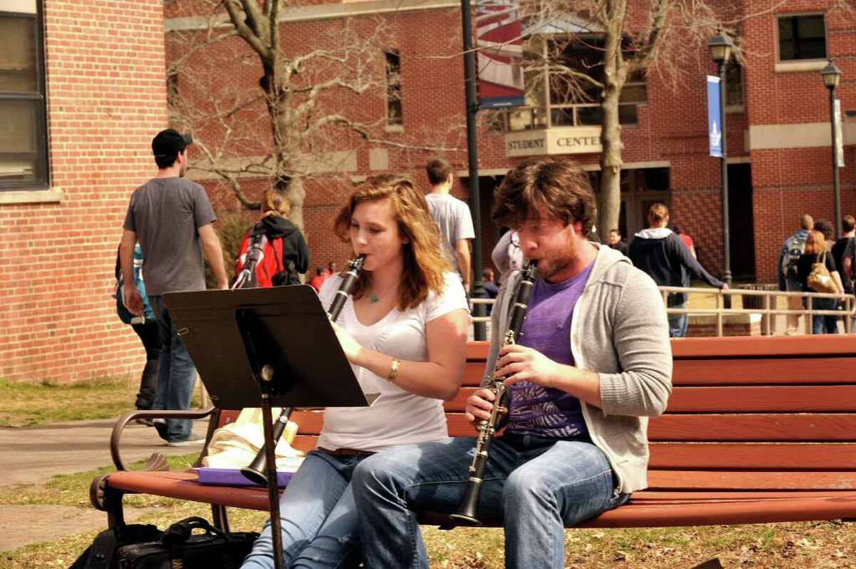 Kate Heidemann, 20, of Norwalk, and Aaron Marshall, 22, of Prospect, play in the sun during the afternoon at Western Connecticut State University's midtown campus Monday, March 12, 2012. Heidemann is practicing for her clarinet recital on may 4th at the Wilton Library.