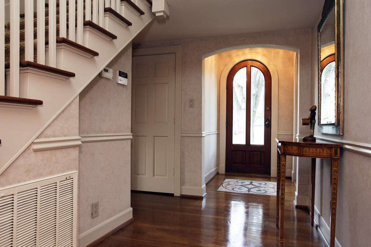 The entryway features hardwood floors, room for a foyer table, and close proximity to the second-floor stairway.