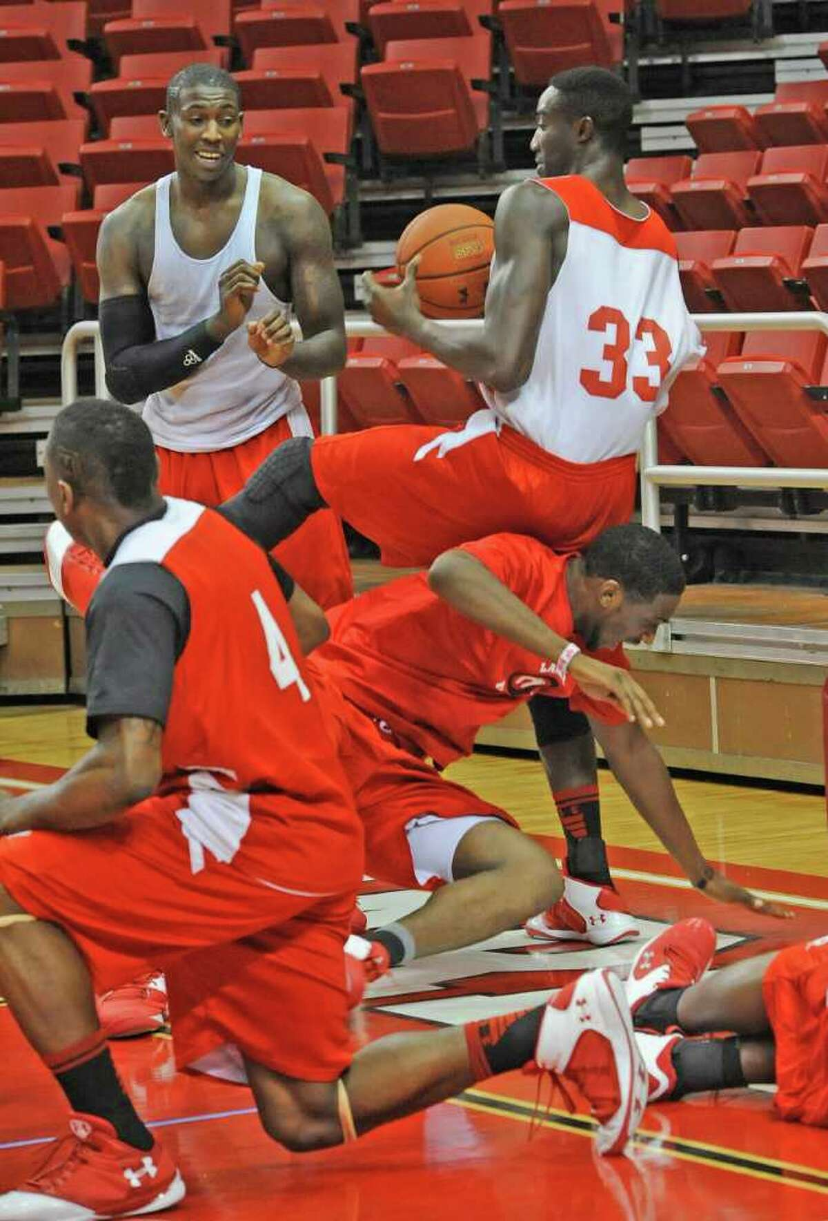 Lamar Cardinal #33, Osas Ebomwonyi, right, holds onto the ball while his teammates fall to the floor chasing it during drills Monday afternoon. After the practice, the Lamar University Cardinal basketball team was leaving the Montagne Center and heading to the Jack Brooks Regional Airport in Nederland to fly to Dayton Ohio for their first NCAA tournament game against Vermont. Dave Ryan/The Enterprise