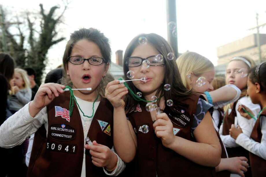 Brownie Girl Scouts Angel Furano and Emily De Mita, both 7, blow bubbles at a ceremony celebrating the 100th year of Girl Scouting in the United States in front of the Greenwich Town Hall Monday, March 12, 2012. Photo: Helen Neafsey / Greenwich Time
