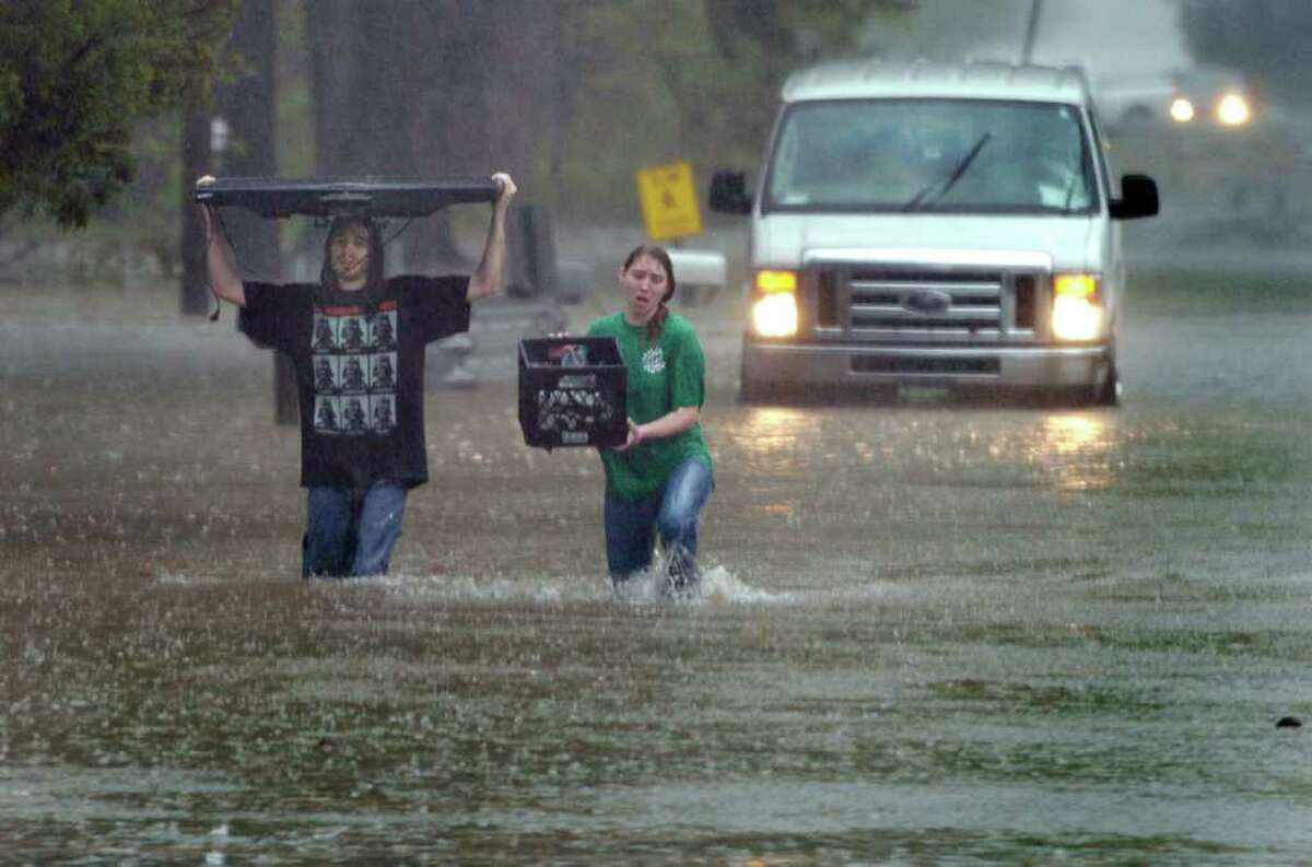 A couple saves their wide-screen TV and a few other possessions as rain pelts Carencro, La., on Monday.