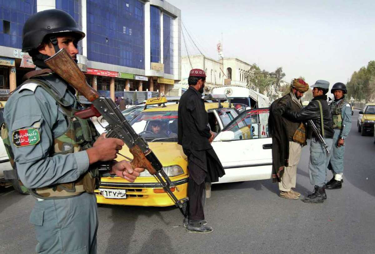 An Afghan policeman, left, stands guard as a colleague, right, searches a taxi passenger at a police checkpoint following Sunday's killing of civilians by a U.S. soldier in Kandahar province, south of Kabul, Afghanistan, Monday, March. 12, 2012. An Afghan youth recounted on Monday the terrifying scene in his home as a lone U.S. soldier moved stealthily through it during a killing spree, then crouched down and shot his father in the thigh as he stepped out of the bedroom. (AP Photo/Allauddin Khan)