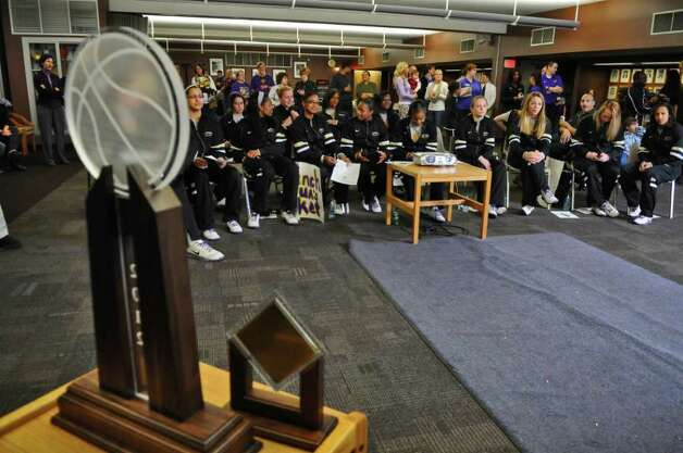 UAlbany women's basketball players anxiously watch a televised NCAA tournament selection show to find out who and where they would be playing , as they sit near the America East championship trophy. They later celebrated after finding out they would be playing Texas A & M this Saturday in Texas in the NCAA Division I women's basketball tournament, on Monday night March 12, 2012 in Albany, N.Y.   (Philip Kamrass / Times Union ) Photo: Philip Kamrass / 00016764A