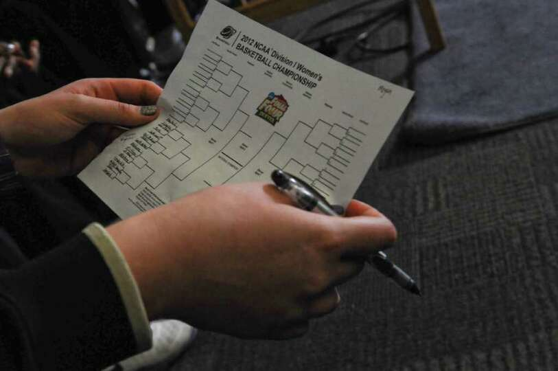 UAlbany women's basketball player Megan Craig fills out her tournament brackets as she and her teamm
