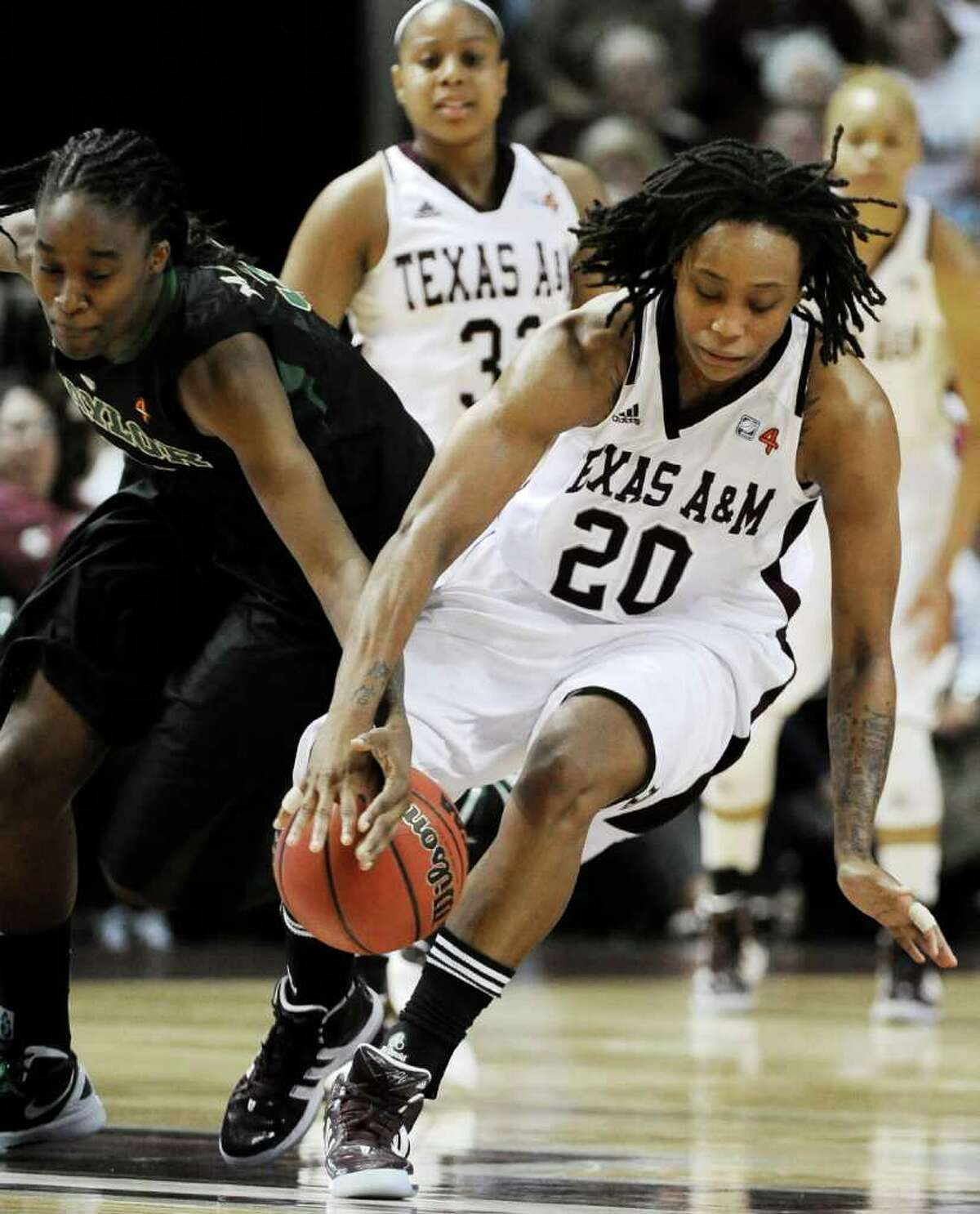 Baylor's Jordan Madden, left, and Texas A&M's Tyra White (20) struggle for possession of the ball in the second half of an NCAA college basketball game Monday, Feb. 27, 2012, in College Station, Texas. Baylor won 69-62.