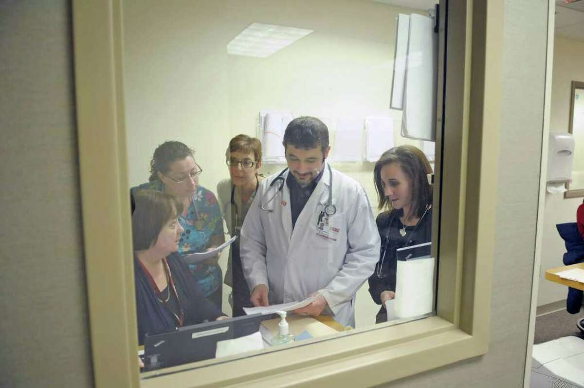 """Latham Medical Group employees, from left, Rose Gepfert, R.N., Kelly Martin, R.N., and a clinical care coordinator, Kelly Martin, R.N., and a patient care coordinator, Heather Whitcomb, R.N., and a patient care coordinator, Dr. Raymond Carrelle and Iccis Vickery, L.P.N., and a patient care coordinator all take part in a """"physician's huddle"""" at a nursing station in Latham, NY. The huddles allow those involved in a patient's care at the practice to come together to discuss treatment plans. (Paul Buckowski / Times Union)"""