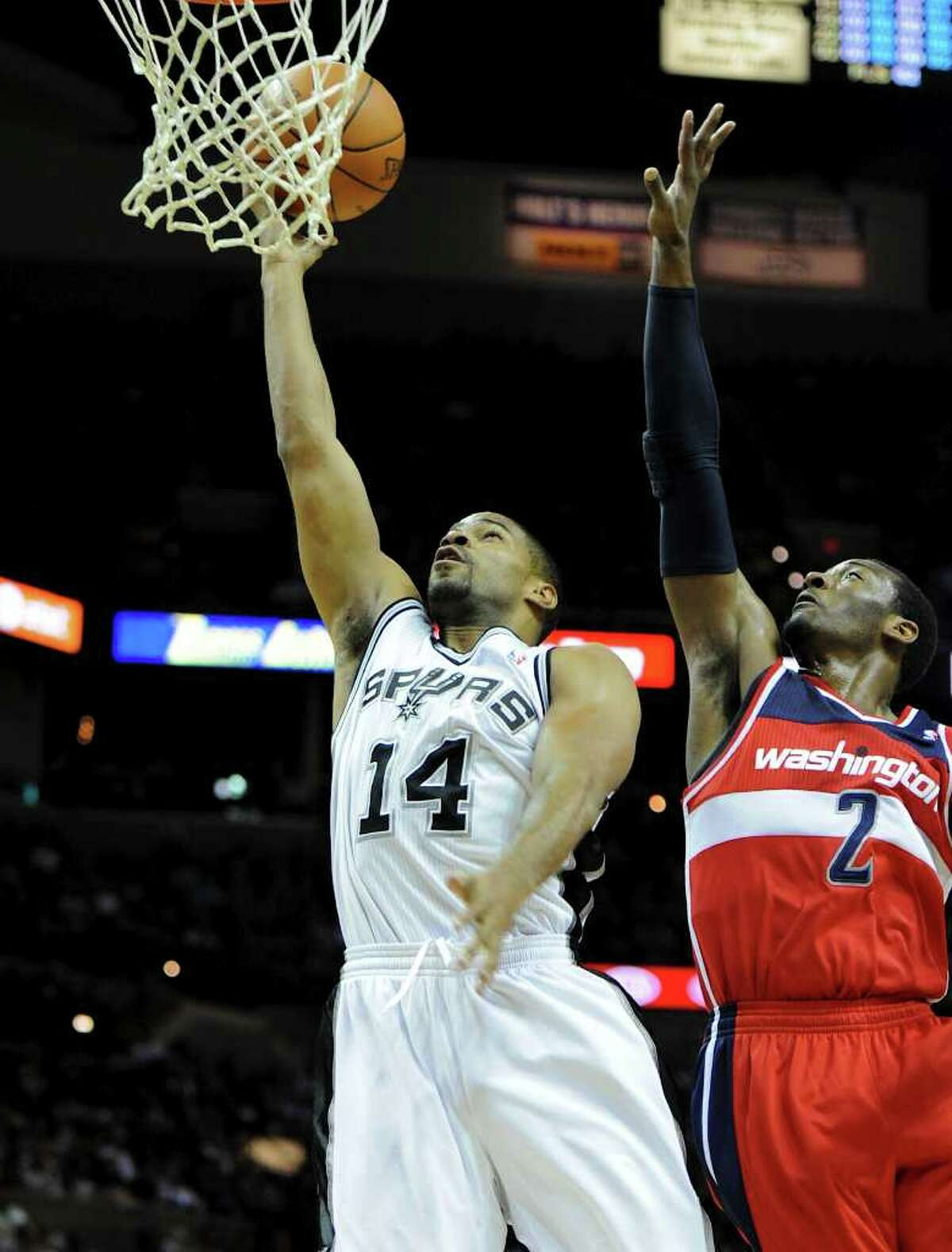 San Antonio Spurs point guard Gary Neal (14) puts up a layup as Washington Wizards point guard John Wall (2) defends during a NBA basketball game between the Washington Wizards and the San Antonio Spurs at the AT&T Center in San Antonio, Texas on March 12, 2012. John Albright / Special to the Express-News.