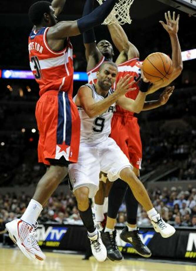 San Antonio Spurs point guard Tony Parker (9) loses control of the ball as he is surrounded by three Washington Wizards  under the basket during a NBA basketball game between the Washington Wizards and the San Antonio Spurs at the AT&T Center in San Antonio, Texas on March 12, 2012.