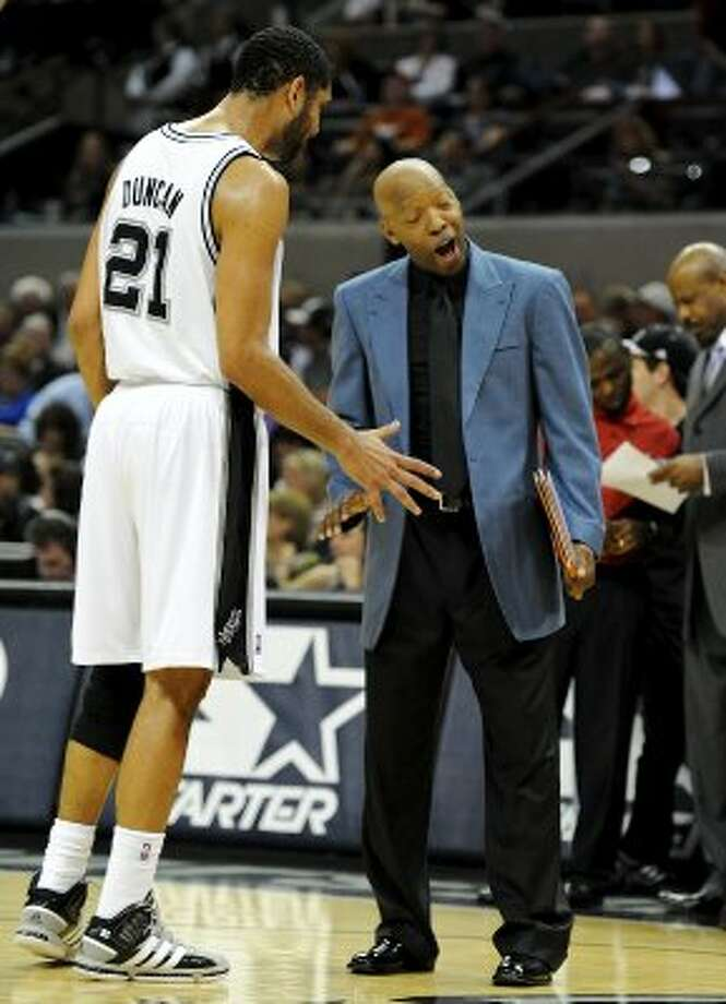 Washington Wizards assistant coach Sam Cassell talks with San Antonio Spurs center Tim Duncan (21) during a time out during a NBA basketball game between the Washington Wizards and the San Antonio Spurs at the AT&T Center in San Antonio, Texas on March 12, 2012.
