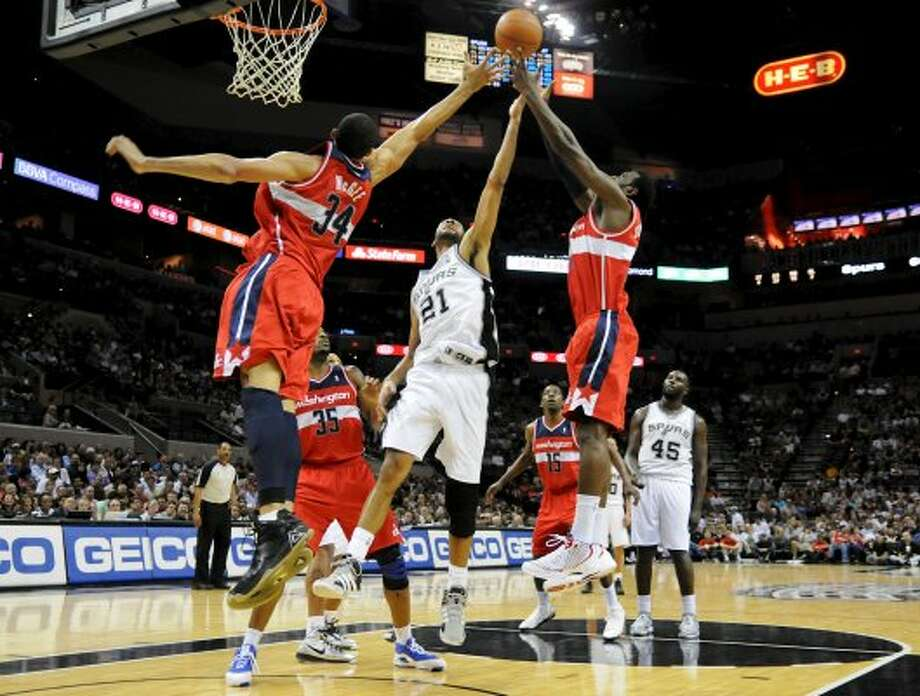 San Antonio Spurs center Tim Duncan (21) tries to grab a rebound between Washington Wizards center JaVale McGee (34) and Washington Wizards small forward Chris Singleton (31) during a NBA basketball game between the Washington Wizards and the San Antonio Spurs at the AT&T Center in San Antonio, Texas on March 12, 2012.