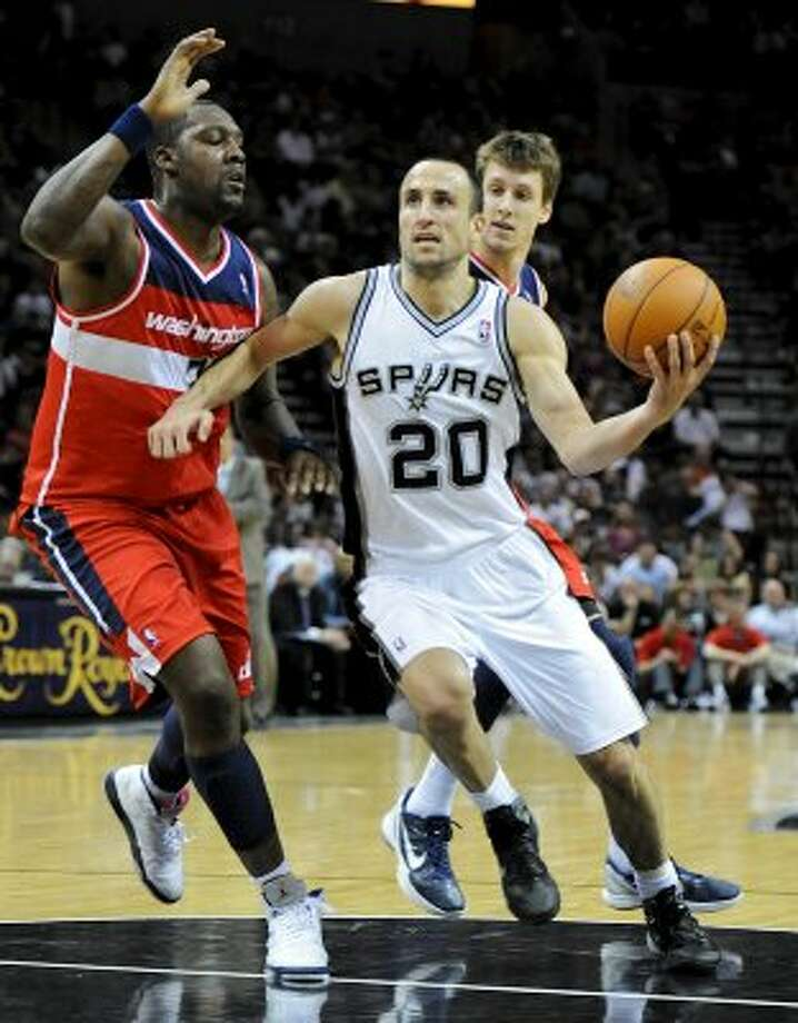San Antonio Spurs shooting guard Manu Ginobili (20) drives into the lane and around Washington Wizards power forward Andray Blatche (7) during a NBA basketball game between the Washington Wizards and the San Antonio Spurs at the AT&T Center in San Antonio, Texas on March 12, 2012.