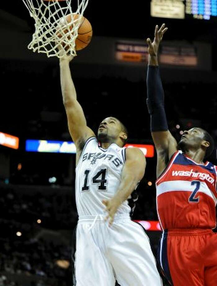 San Antonio Spurs point guard Gary Neal (14) puts up a layup as Washington Wizards point guard John Wall (2) defends during a NBA basketball game between the Washington Wizards and the San Antonio Spurs at the AT&T Center in San Antonio, Texas on March 12, 2012. John Albright / Special to the Express-News. (San Antonio Express-News)