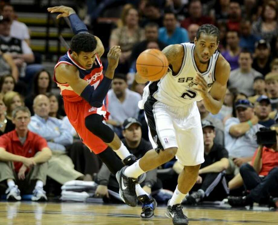 San Antonio Spurs small forward Kawhi Leonard (2) heads up court after stealing the ball from Washington Wizards shooting guard Nick Young (1) during a NBA basketball game between the Washington Wizards and the San Antonio Spurs at the AT&T Center in San Antonio, Texas on March 12, 2012.