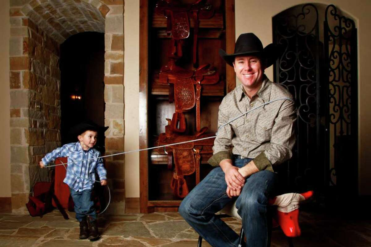 Trevor Brazile poses for a portrait next to a handful of his 8 PRCA All-Around World Title saddles, as his son, Treston, 3, ropes him while at the family home in Decatur. Trevor Brazile is a tie-down and team roper and won 14 world champion titles bestowed by the Professional Rodeo Cowboy Association. He is an eight-time winner of the all-around gold buckle, giving him an edge over fellow Texas Ty Murray. He is on his way to his 15th title and is making his way through this season's Texas rodeos in pursuit of that goal. He has appearances in Fort Worth in January, San Antonio in February and Houston in March.