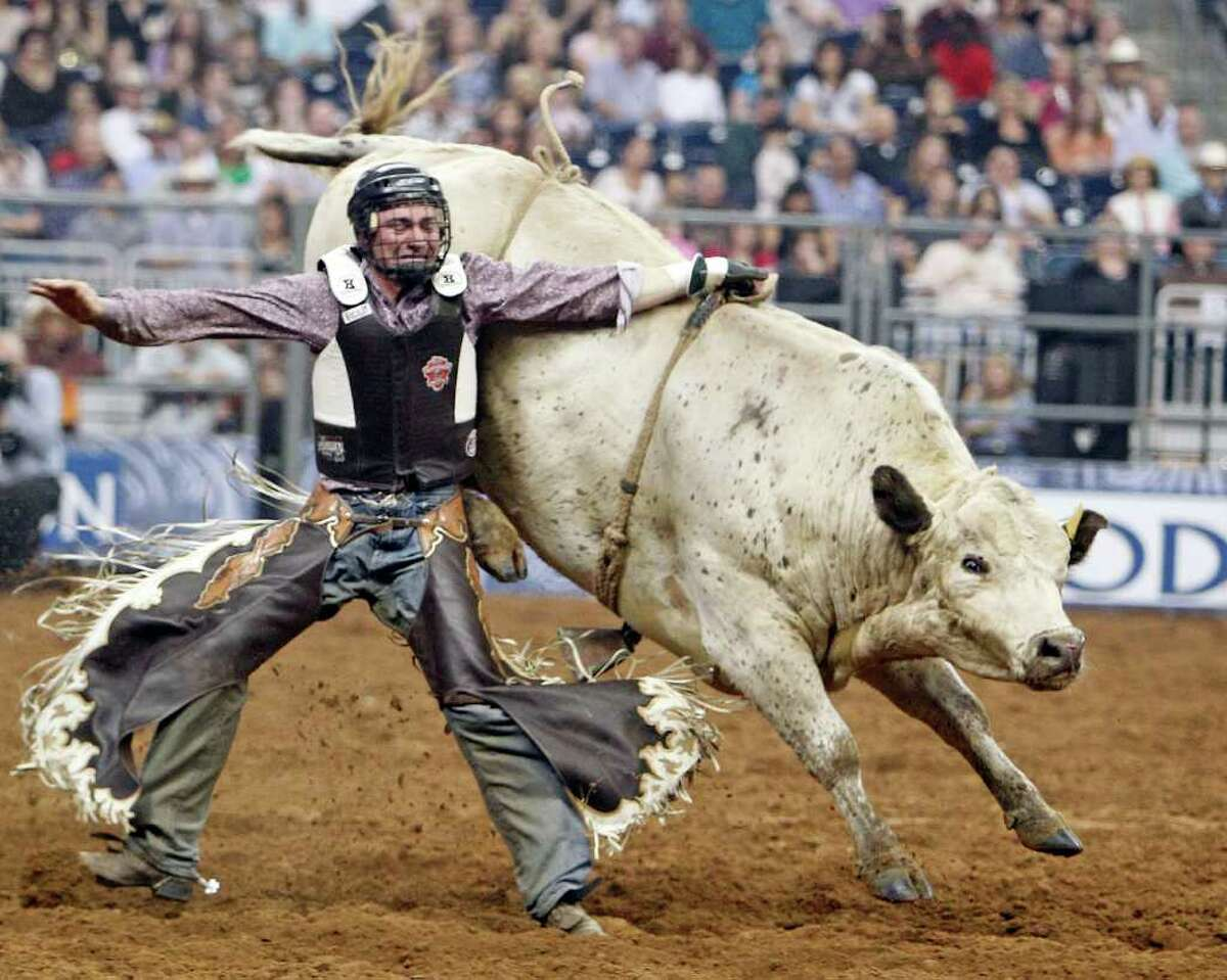Allen Helmuth of Eugene, Ore., tries to clear himself from his rigging after failing to complete his ride in Monday's bull-riding competition at RodeoHouston.