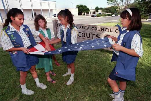 Girl Scout Cadet Krystle Villanueva (from left), Junior Girl Scout Megan Klein and Girl Scout Cadets Vianney Perez and Ana Lisa Harvey fold the Stars and Stripes during a flag lowering ceremony outside the San Antonio Area Council of Girl Scouts building on Flag Day, June 11, 1998. Photo: RICK HUNTER, Express-News File Photo