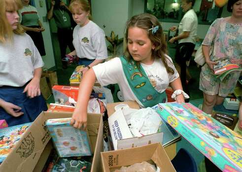Junior Girl Scout Audrey Diehl, 9, unloads donated presents with help from members of the Stevenson Girl Scout Unit Monday, May 24, 1999, at the Baptist Regional Children's Center. Over 75 books, games and videos where collected by the scouts to be used by children at North Baptist Hospital. Photo: Kevin Geil, Express-News File Photo