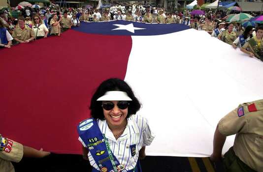 Stephanie Sanchez, from Girl Scout Troop 450, smiles as she and other area scouts carry a Texas flag measuring 20 feet by 38 feet during the 109th annual Battle of Flowers parade in San Antonio on April 28, 2000. Photo: BOB OWEN, Express-News File Photo / SAN ANTONIO EXPRESS-NEWS