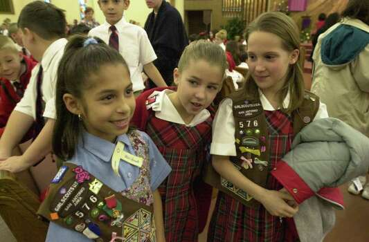 Girl Scout Medal of Honor winner Melani Lozano, left, wears her award as St. Matthew's Catholic School students Kassie Devane and Allison Kincer admire her after an awards ceremony on Friday, Dec. 21, 2001. Photo: BILLY CALZADA, Express-News File Photo