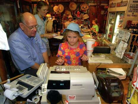 Girl Scout Gina Cramer uses the cash register Friday afternoon, July 18, 2003 at the Waring General Store to ring up her items as store manager Ed Patton watches. Camp counselor Sarah Stone helps keep track of Cramer's money. Photo: WILLIAM LUTHER, Express-News File Photo / SAN ANTONIO EXPRESS-NEWS