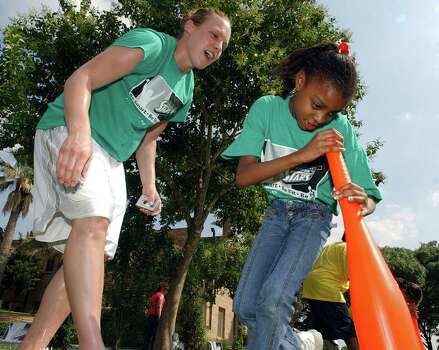 "Silver Stars' Kendra Wecker yells encourgament to Girl Scout Deshaundra Gregory, 9, Troop 172, during a bat race that was part of the ""Be Smart-Be Fit-Be Yourself"" field day Friday, May 20, 2005 at the Red Barry Mansion. Photo: EDWARD A. ORNELAS, Express-News File Photo / SAN ANTONIO EXPRESS-NEWS"