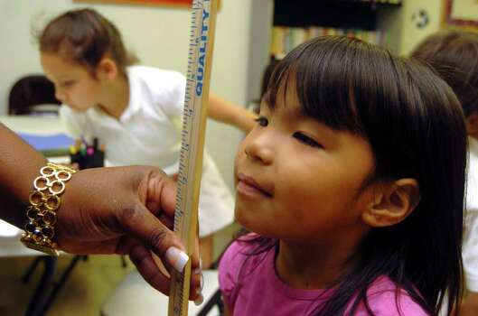 Liliana Garcia, 9, has her height measured during a Girl Scouts afterschool meeting at the Katie M. Jones Girl Scout Center on May 11, 2006. The center, part of the Martin Luther King Service Unit, is receiving a $750,000 Kronsky Grant. Photo: BILLY CALZADA, Express-News File Photo / SAN ANTONIO EXPRESS-NEWS