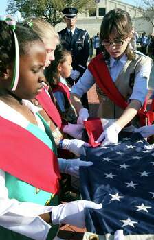 Caitlin Baumgarten, 14, with Girls Scout Troop 614 folds the U.S. Flag during the 58th annual Girls Scouts flag retreat ceremony at Randolph AFB honoring military families and parents while recognizing female contributions to society Tuesday, March 11, 2008. Photo: DELCIA LOPEZ, Express-News File Photo / SAN ANTONIO EXPRESS-NEWS