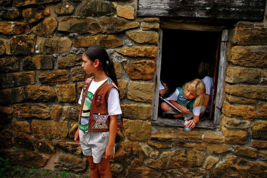 Brownie Lauren Cheever (left), 9, and Girl Scout Addison Nelson, 10, watch a demonstration outside the Indian Quarter Rooms at Mission San José May 17, 2008. Photo: NICOLE FRUGE, Express-News File Photo / nfruge@express-news.net