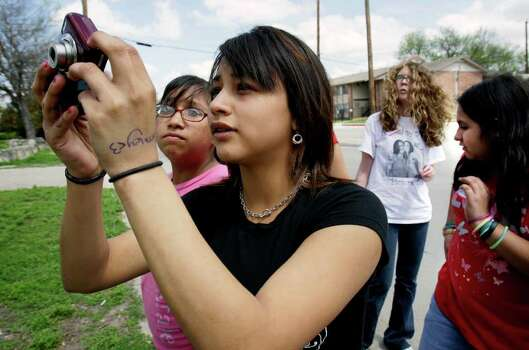 Michelle Luis takes a picture for a Girl Scout project, as Emily Sanchez (left) observes. Girls Scouts take photos on the West Side to document what makes it easy or hard to be physically active in their community, Monday, March 15, 2010. Photo: BOB OWEN, Express-News File Photo / rowen@express-news.net