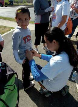 "Jaeden Lopez (left) has a pedometer put on her belt by her sister, Madeline Lopez at Apache Creek Greenway on March 12, 2011, as part of the Girl Scouts ""Be Fit With Friends"" program. Photo: Express-News File Photo"