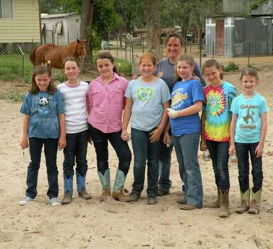Darla Cherry (rear), proprietor of Meadow Haven Horse Rescue in Nixon, poses with volunteers from San Antonio Girl Scout Troop 543 (from left): Audrey Zgardowski, Caroline Vassar, Sarah Katherine Wingrove, Shelby Atherton, Emily Noble, Annie Notzon and Elizabeth Allison. Photo: Courtesy Photo, Courtesy Photo