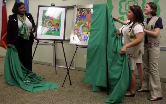 Jackie Gorman, chairman of the board for Girl Scouts of Southwest Texas (left), and Girl Scout Ambassadors Victoria Tovar (center) and Brandy Vickers (right) unveil commemorative posters celebrating the 100th year of Girl Scouts at a celebration Monday, March 12, 2012, at the Sally Cheever Girl Scout Leadership Center. The poster is by Fiesta San Antonio poster artist Shelley Fluke. Photo: San Antonio Express-News