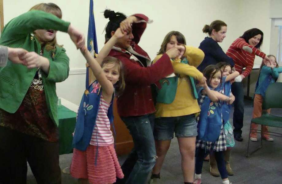 Participants in the Fairfield celebration of the 100th anniversary of the Girl Scouts on Monday evening at the Fairfield Public Library followed tradition by twisting out of a Friendship Circle. Photo: Meg Barone / Fairfield Citizen freelance
