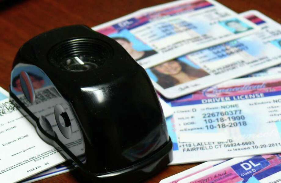 Some of the fake IDs confiscated by police, and a handheld black light that picks up the holograms that a real ID should have Photo: Genevieve Reilly / Fairfield Citizen