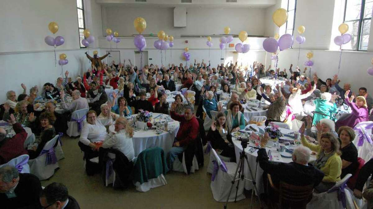After helping themselves to a brunch buffet, residents of The Marvin and family members show their excitement that the organization reached its 15-year anniversary by throwing their hands in the air.