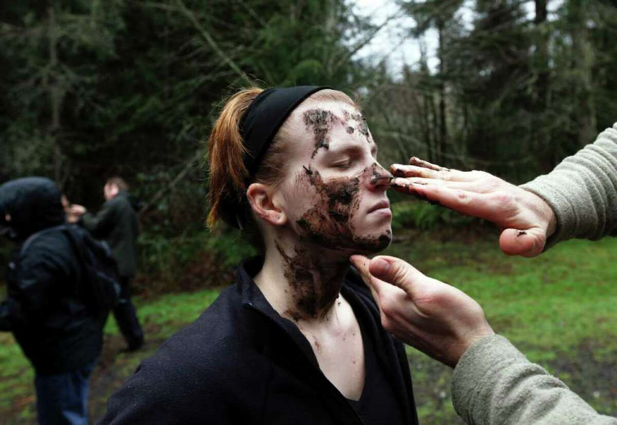 """Natasha Raedel gets her face coated with mud at a """"Zombie First Responder"""" class where students learned to use mud as camouflage in the forest."""