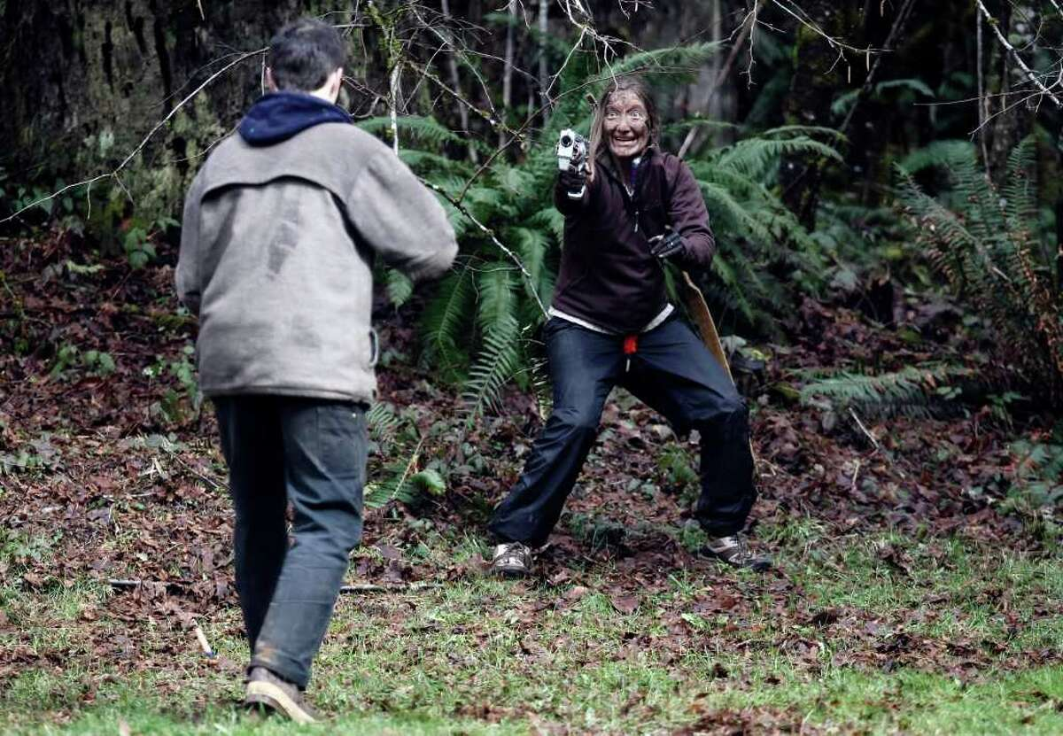 """Mad bo staff skills won't be enough when the dead walk. Take a look as would-be first responders prepare to battle the zombie horde. Above, Jocelyn Moore (R), a participant at a """"Zombie First Responder"""" class use toy guns to attack a zombie (L) on Sunday, March 11, 2012, in Sandy, Ore. In an intensive 2-day curriculum participants train in everything from wilderness and urban survival, nerf or nerd weaponry, stealth and evasion, and proper zombie """"disposal""""."""