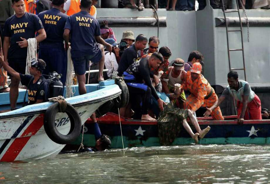 Rescuers recover the body of a victim of a ferry accident on the banks of the Meghna River in Munshiganj district, about 20 miles south of Dhaka, India, Tuesday. A ferry packed with about 200 people capsized in a river in southern Bangladesh on Tuesday, killing 31 people and leaving dozens more missing, authorities said. Photo: AP