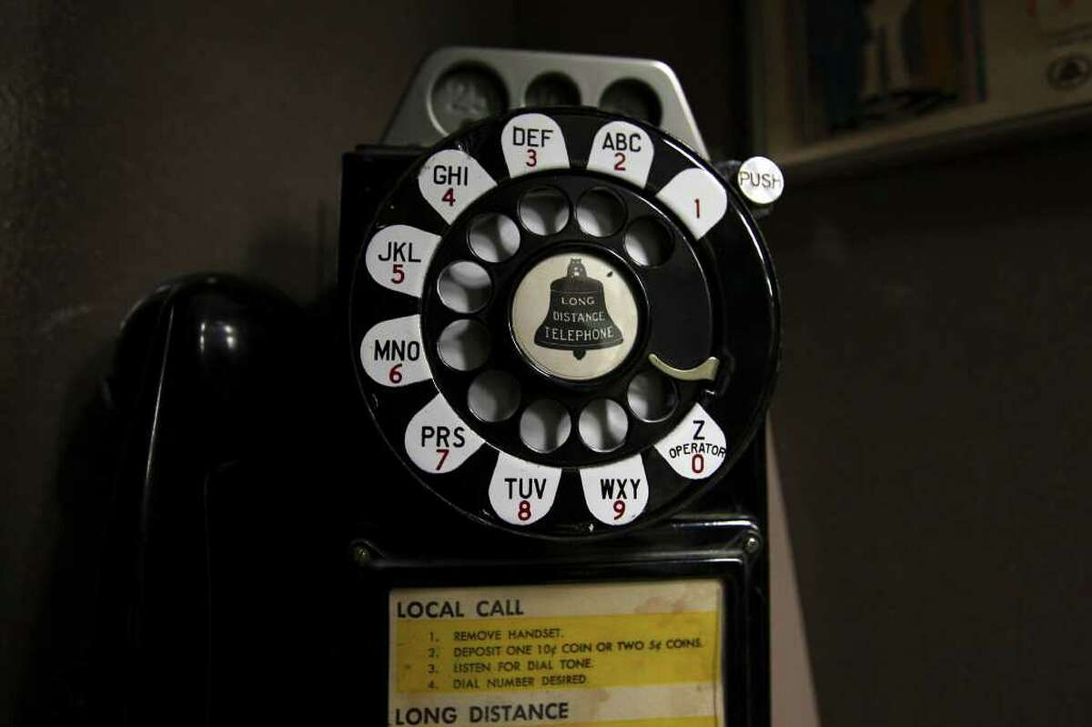 A detail of a rotary phone in a booth that is part of Flood's telephone collection.