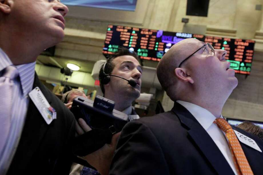 Trader Gregory Rowe, center, and specialist Peter Kennedy, right, check prices as they work on the floor of the New York Stock Exchange Tuesday, March 13, 2012. Strong February retail sales results drove U.S. stocks higher at the opening of trading. (AP Photo/Richard Drew) Photo: Richard Drew / AP