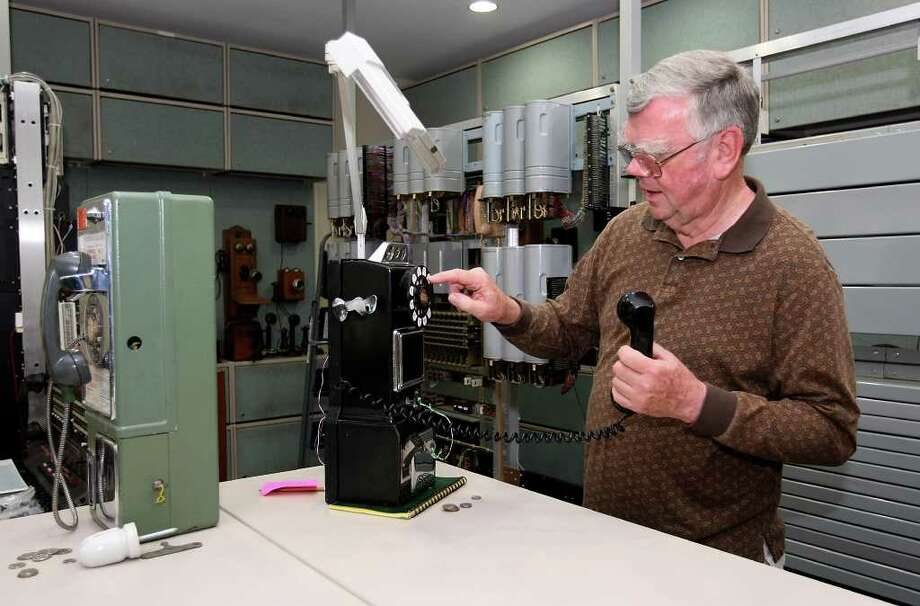 Father Peter Flood became interested in telephones as a child and has  widened  that interest to include old switchboards and telephone exchange systems. Photo: Jerry Lara, San Antonio Express-News / © San Antonio Express-News