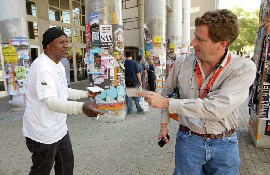 Clarence Jones (left) hawks Wi-Fi connectivity for donations outside the Convention Center in Austin. Photo: Alberto Martinez, Austin American-Statesman