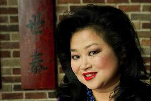 Gigi Huang poses for a photo holding a dish of Orange Beef Tuesday, March 6, 2012, in Houston. This is a dish that her father had on his menu for years before it closed. When she opened her restaurant in the Galleria, it was not on the menu, but her father's loyal customers insisted she serve it. It is now on the menu during lunch only. ( Brett Coomer / Houston Chronicle )