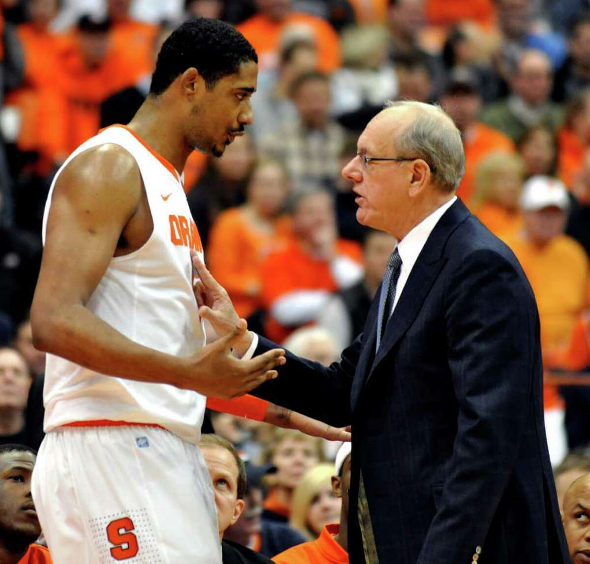 FILE - In this Jan. 15, 2011, file photo, Syracuse head coach Jim Boeheim, right, talks with Fab Melo during the first half against Cincinnati in an NCAA college basketball game in Syracuse, N.Y. Melo did not travel with the team to Pittsburgh and the university says he won't take part in the NCAA tournament due to an eligibility issue. The school would not elaborate.