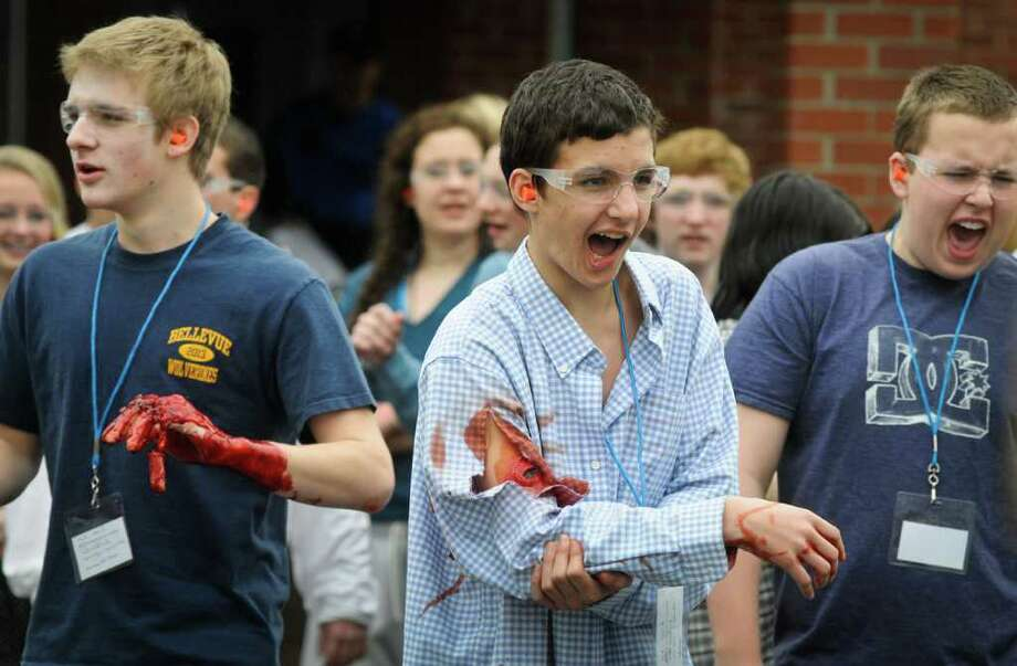 From left: Matt Mckenna, 16, Tristan Jones, 14, and Grant Neuman, 15, pretend to be injured during a multiple shooter drill at Bellevue High School on Saturday, March 10, 2012. Planned since August, the drill tested the response and teamwork capabilities of many fire and police departments from across Western Washington. Dozens of Bellevue High School students were made up with fake wounds to make the drill more realistic, but had to wear glasses and earplugs for safety reasons. (Photo by Lindsey Wasson Photo: LINDSEY WASSON / SEATTLEPI.COM